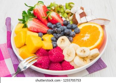 fruit salad with fresh berries, orange, coconut, mango, and sliced of banana