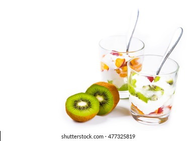 Fruit salad in glass goblets of kiwi and peaches with yogurt isolated on white