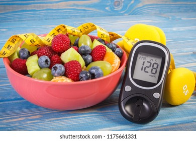 Fruit salad, glucose meter with result of sugar level, tape measure and dumbbells for fitness, concept of diabetes, sport, diet, slimming, healthy lifestyles and nutrition