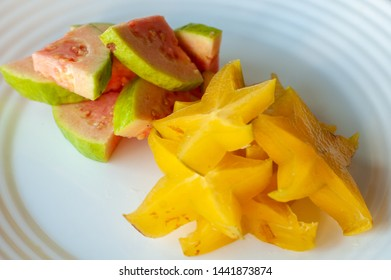 Fruit salad with guava and carambola, carambola and organic guava on white plate, slices of carambola and red guava, red guava fruit salad.  Star fruit.