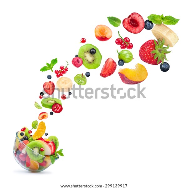 fruit salad ingredients in the air in a glass bowl isolated on white background