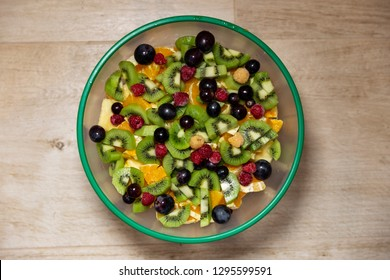 Fruit salad made of kiwi, orange, grapefruit, raspberry and apple in a large bowl on a wood table
