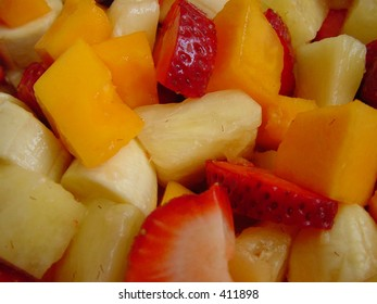 Fruit salad made of strawberries, papaya, bananas and pineapple.