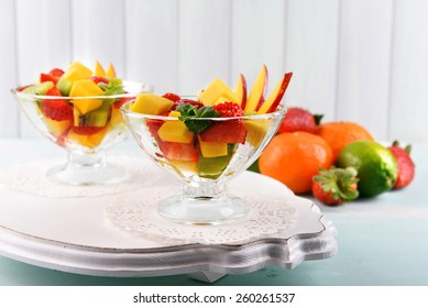 Fruit salad with mint in glassware on wooden table and planks background