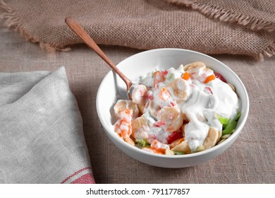 fruit salad of oranges, grapefruit, bananas, kiwi dressed with natural yoghurt and sprinkled with chopped Apple