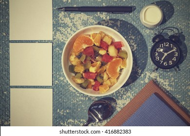 Fruit salad and a piece of paper to take notes. The concept: a daily routine.