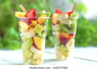 Fruit salad in plastic cups takeaway. Sliced organic fruits and berries, healthy snack to go, copy space.
