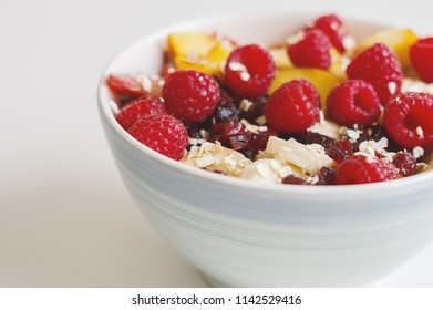 Fruit salad with raspberry, nectarine, banana, plum, dried cranberry and oats. Oats porridge with fruits and berries. Healthy eating concept