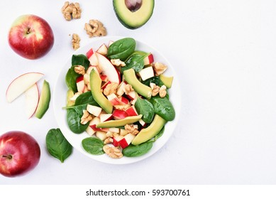 Fruit salad with red apples, avocado, spinach and walnut on light background with copy space, top view. Flat lay.