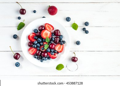 Fruit salad with strawberries, blueberries and sweet cherries. Top view, flat lay