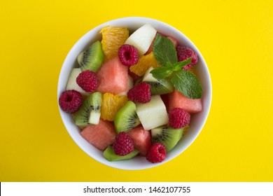 Fruit  salad in the white  bowl on the yellow  background. Top view.