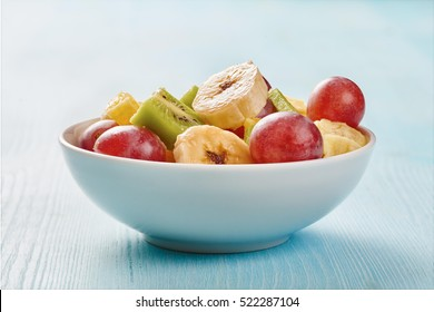 Fruit salad in white bowl on wooden blue table