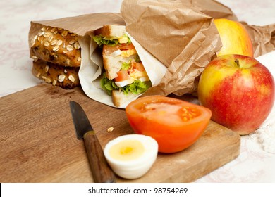 Fruit, sandwiches and buns in a brown paper lunch bag