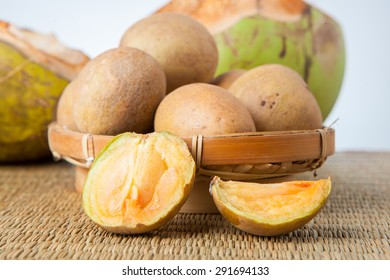 Fruit Sawo Sapodilla peeled with coconut on white background