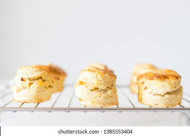 Fruit scones - Three homemade sweet scones on the cooling track, side view on the white background