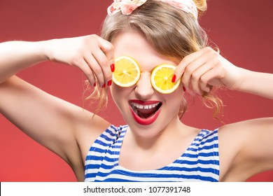 Fruit Series. Portrait of Smiling Passionate Caucasian Blond Posing With Two lemon Slices in Front of Eyes. Against Red Background.Horizontal Image