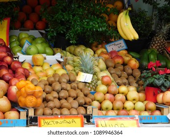 "Fruit shop with red,green and jonagold apples,tangerines,kiwis,pears,pineapples, oranges,bananas avocados and a pot with cyclamen flowers. The signs translate to ""apples,Jonah apples,kiwis,apples"""