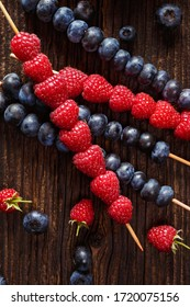 Fruit skewers with fresh raspberries and blueberries on a wooden background top view, close up
