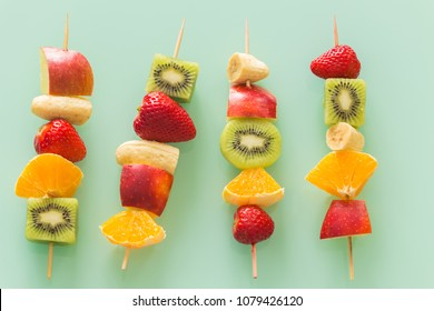 fruit skewers on the pastel green glass background / concept of healthy eating