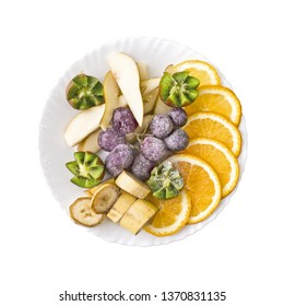 Fruit slices orange, grapes, kiwi, pear and banana, on a plate isolated.
