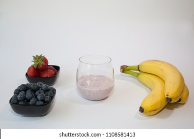 A fruit smoothie in a clear glass with blueberries, strawberries and bananas.