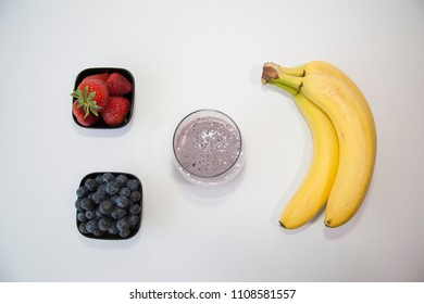 Fruit smoothie in a clear glass made from blueberry, banana and strawberry.
