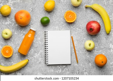 Fruit smoothie drink recipe. Blank notebook, bottle with juice and fruits variety on gray table, top view, copy space