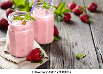 Fruit smoothie with mint leaves on wooden rustic table.