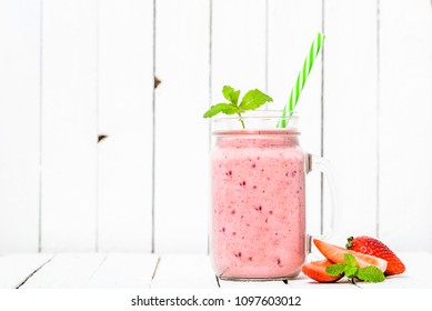Fruit smoothie with strawberries, milkshake with strawberry blended in jar on white background. Vegan diet and healthy lifestyle concept.