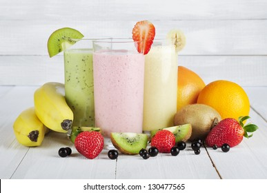 Fruit smoothies with black currant, strawberry, kiwi, orange and banana  on white wooden background