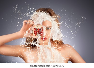 Fruit splash. A portrait of a nude hot model with a pomegranate's half in her hand in milky splash.