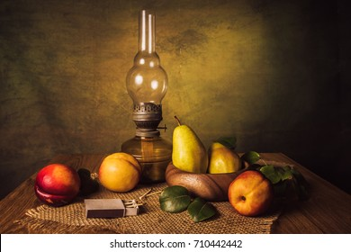 Fruit still life with pears, nectarines and an old kerassene lamp