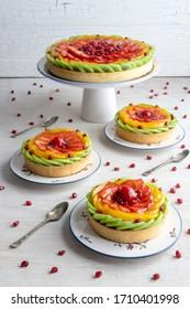 Fruit tart with kiwi, peaches, strawberries, raspberries and grenade seeds