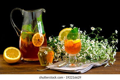 Fruit tea with lemon, medicinal plants and honey,before black background with white flowers