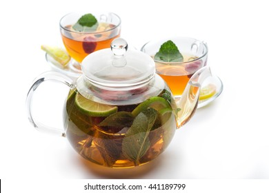 Fruit tea with mint leaves in a teapot on a white background