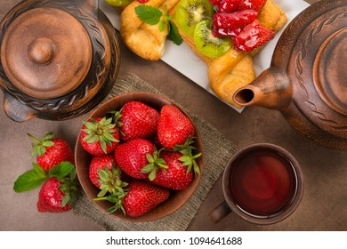 Fruit tea and sweet bakery with strawberry, kiwi in sugar glaze. Summer dessert food. Top view.