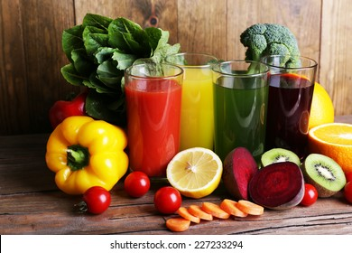 Fruit and vegetable juice in glasses and fresh fruits and vegetables on wooden table on wooden wall background