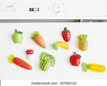 Fruit and vegetable magnets on a white refrigerator.