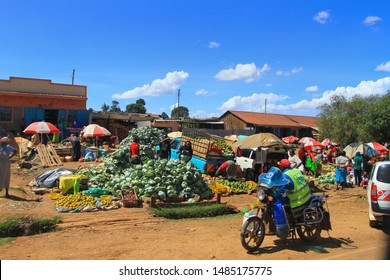 Fruit and vegetable market, village Kenya, East Africa. February 2019, Local Kenyan people buying and selling outdoors. Lots of cabbage, parasols and motorbike.  Travel by road through Kenya.