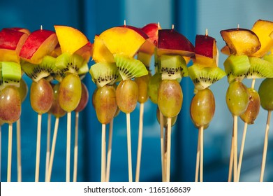 fruit vegetarian canape at skewers with grapes, kiwi and peach at pure blue background. catering snack