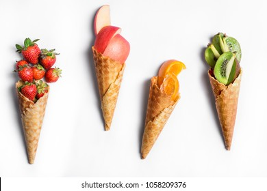 Fruit in waffle cones isolated on white background - healthy ice cream options.
