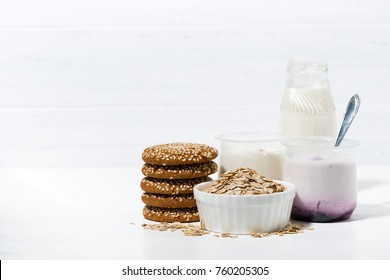fruit yoghurt and oatmeal cookies - healthy food on white table, horizontal