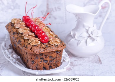 Fruitcake decorated walnuts, almond and cocktail cherries on the white plate