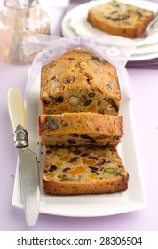 fruitcake partially sliced and decorated with ribbon