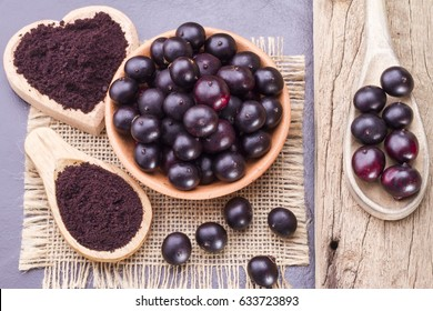 Fruits and acai powder originating from the Amazon on wood (Euterpe oleracea)
