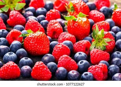 Fruits background, strawberries, raspberries, blueberries