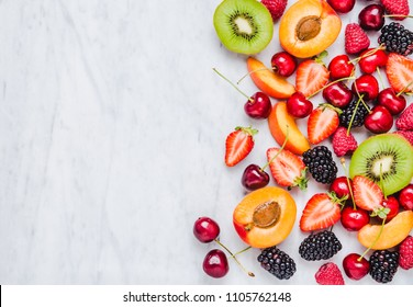 Fruits and berries with copy space on white marble table top view.