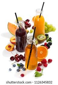 Fruits, berries and delicious array of fresh fruit juices served in glass bottles with drinking straws isolated on white background.