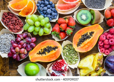 Fruits, berries, nuts, seeds top view on wood background.Healthy, detox, superfood concept.