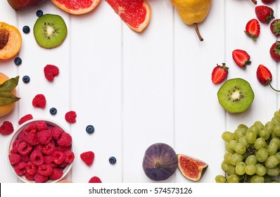 Fruits and berries on the white wooden background, top view